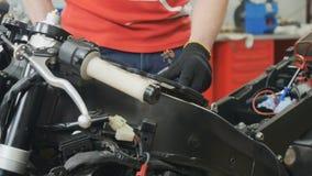 El ingeniero ajusta el filtro de aire en moto almacen de video