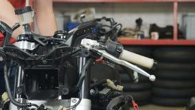 El ingeniero ajusta el motor de la motocicleta metrajes