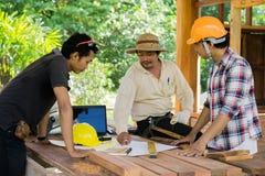 El ingeniero asiático de la carpintería está planeando un trabajo de construir un edificio fotos de archivo