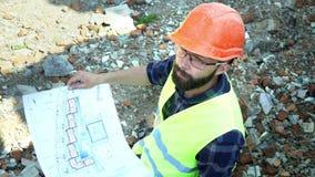 El ingeniero barbudo del constructor analiza el dibujo del edificio, en el fondo de los ladrillos del edificio destruido metrajes