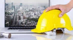 El ingeniero civil está cogiendo el casco de seguridad con el fondo de la ciudad de Tokio imágenes de archivo libres de regalías