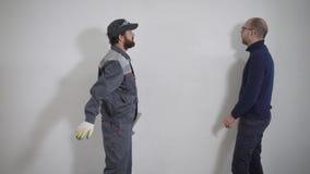 El ingeniero comunica con el constructor sobre la reparación del apartamento, los hombres conduce un diálogo cerca de la pared almacen de metraje de vídeo