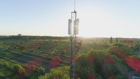 El ingeniero con el artilugio trabaja en torre de comunicación de la antena y muestra el pulgar para arriba en el fondo del paisa almacen de video