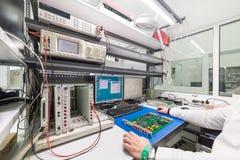 El ingeniero conduce una prueba de los módulos electrónicos acabados Laboratorio para probar y el ajuste de electrónico Imagen de archivo