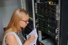 El ingeniero It de la mujer joven entre el servidor atormenta en el CEN de los datos Imagen de archivo libre de regalías