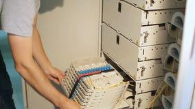 El ingeniero de la red abre una caja con un patchcord óptico en el cuarto del servidor almacen de metraje de vídeo