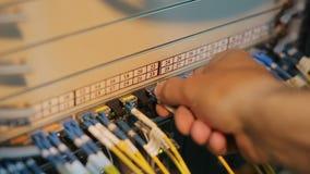El ingeniero de la red en sitio del servidor trabaja con patchcord óptico y el módulo óptico almacen de metraje de vídeo