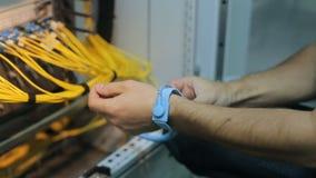 El ingeniero de la red en sitio del servidor trabaja con patchcord óptico y el módulo óptico Llevando una pulsera antiestática a  metrajes
