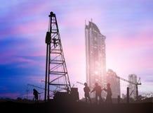 El ingeniero de la silueta que mira cargadores y los camiones en un edificio se sientan Fotografía de archivo libre de regalías