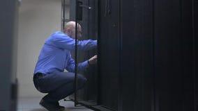 El ingeniero de las TIC abre el gabinete del servidor y enchufa el cable de la red en el interruptor almacen de video