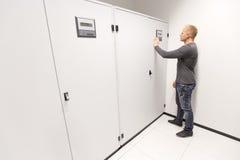 El ingeniero de las TIC ajusta el acondicionador de aire en datacenter imagen de archivo libre de regalías