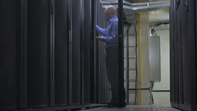 El ingeniero de las TIC en una camisa azul con una libreta, abre el gabinete del servidor en sitio del servidor almacen de metraje de vídeo