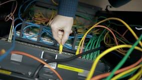 El ingeniero de las TIC enchufa el cable almacen de video