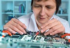 El ingeniero de sexo femenino caucásico de mediana edad o la tecnología repara el mot culpable fotografía de archivo