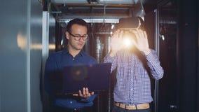 El ingeniero de sexo masculino controla la experiencia de su colega en vidrios virtuales de un ordenador metrajes