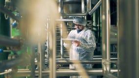 El ingeniero de sexo masculino está actuando una tableta mientras que se coloca en una unidad de la fábrica de la cervecería almacen de metraje de vídeo