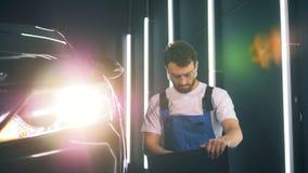 El ingeniero de sexo masculino está examinando un automóvil con su ordenador portátil almacen de metraje de vídeo