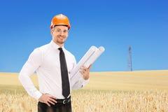 El ingeniero de sexo masculino que celebra la construcción planea en un campo Fotografía de archivo libre de regalías