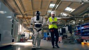 El ingeniero de sexo masculino y un robot están caminando a lo largo de la fábrica metrajes