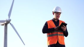 El ingeniero del aspecto caucásico en un casco y el chaleco miran el trabajo del molino de viento, mirando la tableta almacen de video