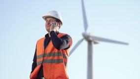 El ingeniero del aspecto caucásico está cerca del molino de viento y de hablar en un teléfono celular metrajes