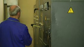 El ingeniero del electricista apaga el panel eléctrico y registra las lecturas de aparatos eléctricos en el tablero del panel metrajes