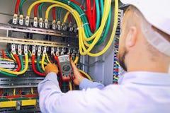 El ingeniero del electricista mide voltaje con el multímetro en gabinete de alto voltaje Fotos de archivo