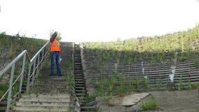El ingeniero del inspector desciende las escaleras y examina el lugar para la construcción, va abajo de las escaleras almacen de metraje de vídeo