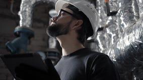El ingeniero del técnico en un casco trabaja en un cuarto de caldera con una tableta almacen de metraje de vídeo