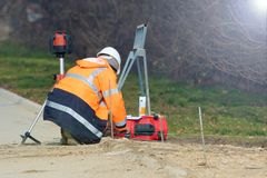El ingeniero del topógrafo realiza la medida geodésica Foto de archivo