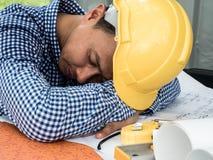 El ingeniero duerme en la tabla mientras que trabaja fotos de archivo libres de regalías