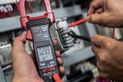 El ingeniero eléctrico es equipo eléctrico del control con un multímetro fotografía de archivo libre de regalías