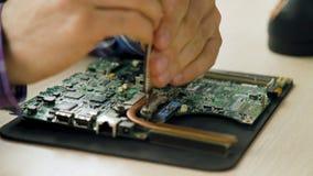 El ingeniero electrónico de la reparación desmonta la placa madre almacen de metraje de vídeo