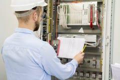 El ingeniero en el casco blanco lee el dibujo de estudio contra el panel industrial eléctrico El trabajador del servicio analiza  imagenes de archivo