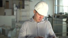 El ingeniero en el casco de protección está utilizando una tableta en una fábrica de la industria pesada A cámara lenta almacen de metraje de vídeo