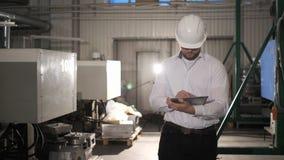 El ingeniero en casco se está moviendo a través de una fábrica de la industria pesada con una tableta A c?mara lenta metrajes