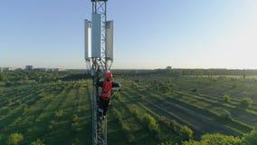 El ingeniero en chaleco y casco de la seguridad sube arriba en la antena celular, opinión del abejón de la torre de la telecomuni almacen de video