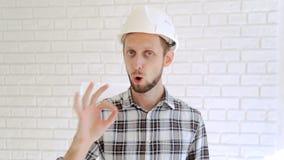 El ingeniero en gestos del casco de protección manosea con los dedos para arriba y aprueba metrajes