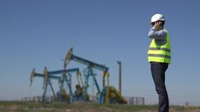 El ingeniero en el teléfono cerca de las bombas de aceite que divulgan las instalaciones disponibles de la extracción del petróle almacen de metraje de vídeo