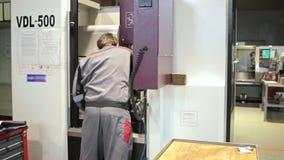El ingeniero está poniendo la máquina del torno del CNC y está comprobando tiempo en fábrica almacen de metraje de vídeo