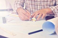 El ingeniero está trabajando en el escritorio con plan del dibujo Imagen de archivo