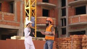 El ingeniero estructural y el arquitecto vestidos en chalecos anaranjados del trabajo y palos duros discuten proceso de la constr almacen de metraje de vídeo