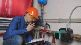 El ingeniero examina la caldera de gas almacen de metraje de vídeo