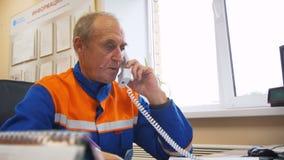 El ingeniero gris-cabelludo de mediana edad contesta a llamada telefónica en oficina almacen de video