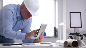 El ingeniero hace el cálculo y el acceso información técnica usando la tableta de tacto almacen de metraje de vídeo