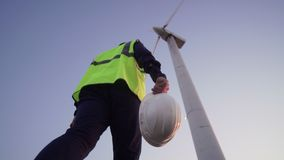El ingeniero Hold en sus manos un casco blanco y pasos adelante al molino de viento delante de él almacen de video