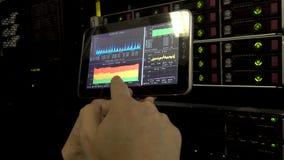 El ingeniero Holds hace tabletas la PC y hace un diagnóstico Ingeniero de las TIC en sitio del servidor Con una tableta a disposi almacen de video
