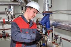 El ingeniero industrial fija el manómetro en sistema de calefacción del tubo Fotos de archivo