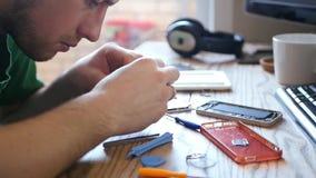 El ingeniero joven de sexo masculino recoge el teléfono celular quebrado, da vuelta al destornillador 1920x1080, hd almacen de metraje de vídeo