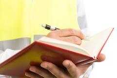 El ingeniero o el arquitecto da llevar a cabo orden del día y la escritura de planes fotografía de archivo libre de regalías